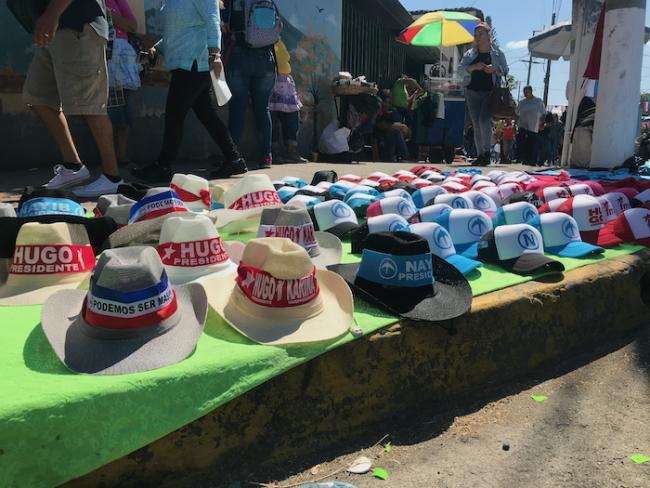 """Se venden gorros y sombreros con los logos partidarios, incluido la letra """"N"""" de Nayib, durante las elecciones presidenciales, 3 de febrero 2019, San Salvador. (Heather Gies)"""