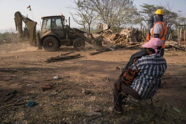 In Roche, a woman watches as her house, which belonged to her family for many generations, is demolished during a forced displacement. (Photo by Rafael Ríos)