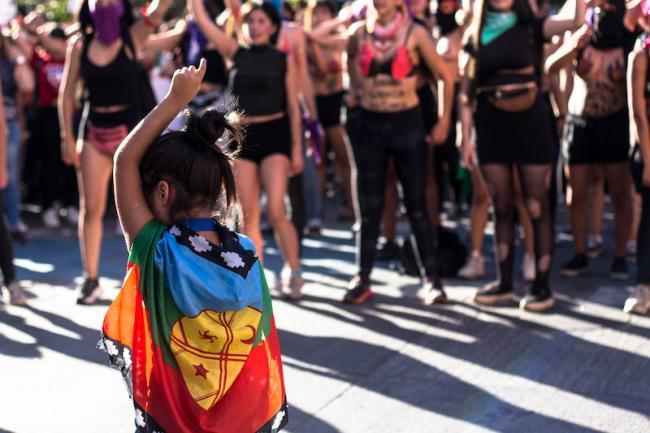 """Una pequeña con la bandera Mapuche se une a la viralizada intervención """"Un violador en tu camino"""" en el Día Internacional de la Mujer en Concepción, Chile, el 8 de marzo 2020. (Isis Fuentealba Quiñones / Wikimedia)"""