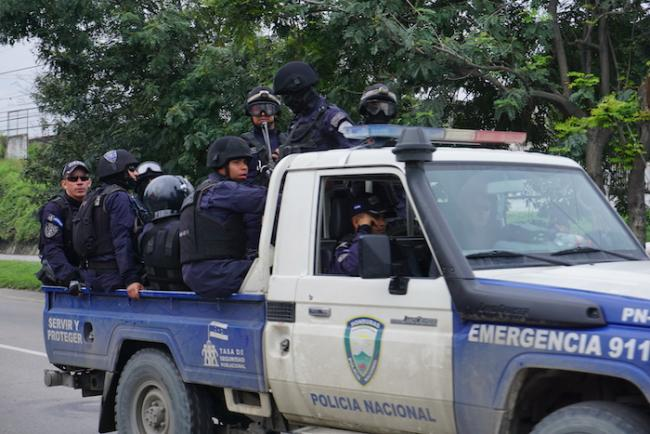 A National Police vehicle loaded with officers drives on the highway to Puerto Cortés in 2018. (Amelia Frank-Vitale)