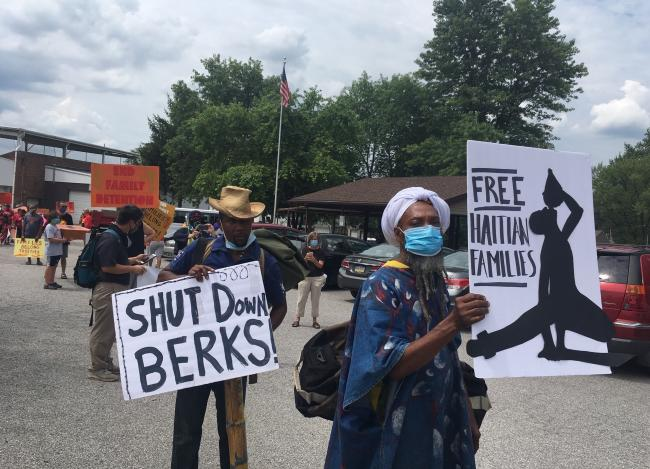 """Demonstrators march to the home of the Pennsylvania governor to demand the shutdown of Berks County Detention facility in September 2020. Signs read """"Free Haitian families"""" and """"Shut down Berks."""" (Haitian Women for Haitian Refugees)"""