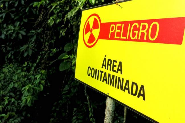 A danger sign warns of contamination in Shushufindi in Ecuador's Amazon, where Chevron left behind toxic waste. (Photo by Xavier Granja Cedeño-Cancilleria del Ecuador/Flickr)