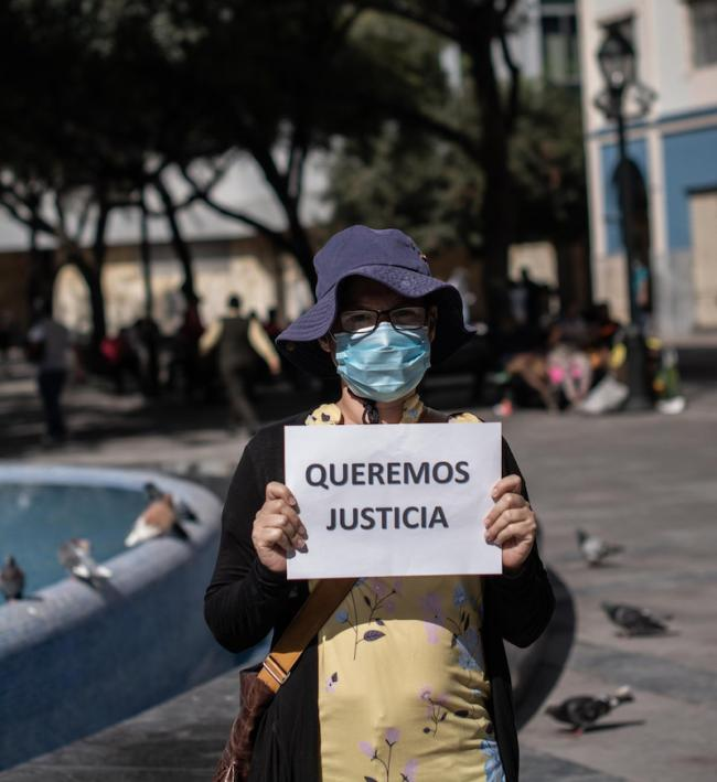 "A protester holds a sign reading ""We want justice"" in Plaza Rocafuerte in the heart of downtown Guayaquil. Groups have protested weekly to highlight cases of disappeared Covid-19 infected bodies. (Andrés Loor / CDH)"