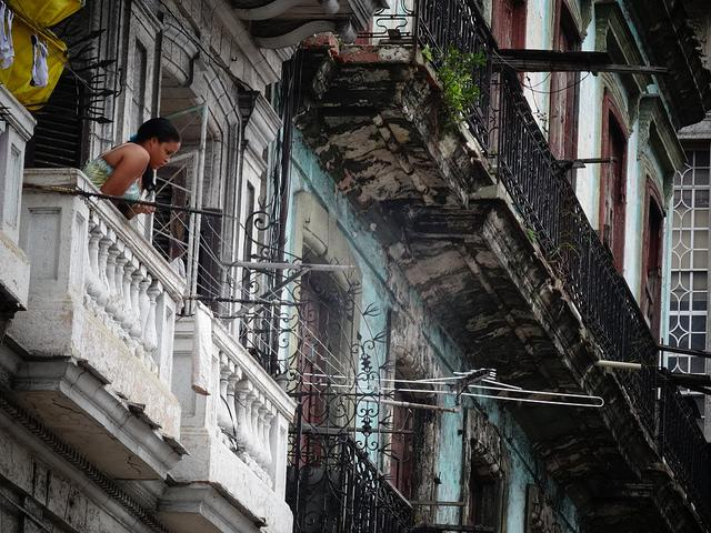 A woman looks out from her balcony toward the Capitol in Havana in 2014. (Flickr/Javier Ignacio Acuña Ditzel)
