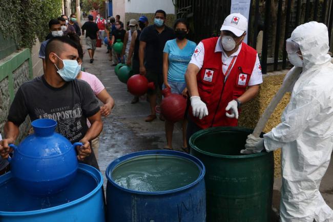 Vecinos de una zona de San Salvador recogen agua distribuida por la Cruz Roja Salvadoreña en marzo de 2020. (Cruz Roja Salvadoreña / Facebook)