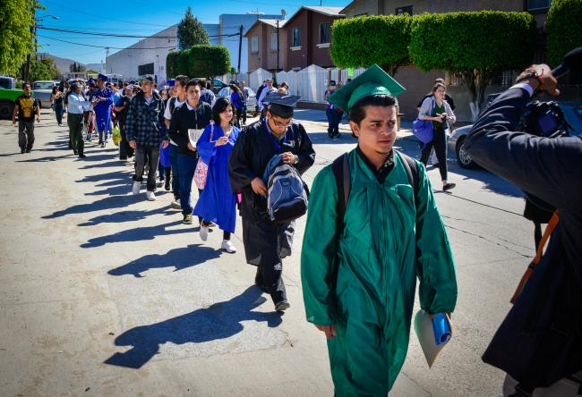 Undocumented activists and DACA recipients cross the U.S.-Mexico border in graduation robes as part of a 2014 action (Steve Pavey/Hope in Focus Photography)