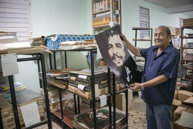 "Rafael Enríquez Vega, OSPAAAL designer and illustrator, holds up his poster ""Smiling Che"" in the repository of the Tricontinental magazine in June 2019. (Photo by Fernando Camacho Padilla)"