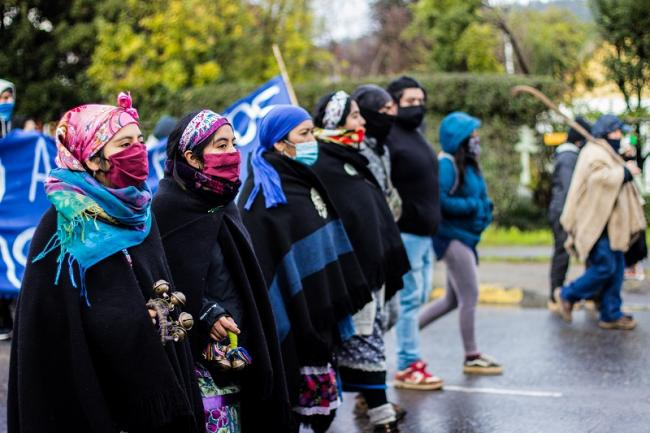 Mapuche women raise their fists as a sign of resistance during the occupation of the Gendarmería offices and mobilizations for Mapuche political prisoners on hunger strike. Cañete, Wallmapu. July 2020. (Julio Parra)
