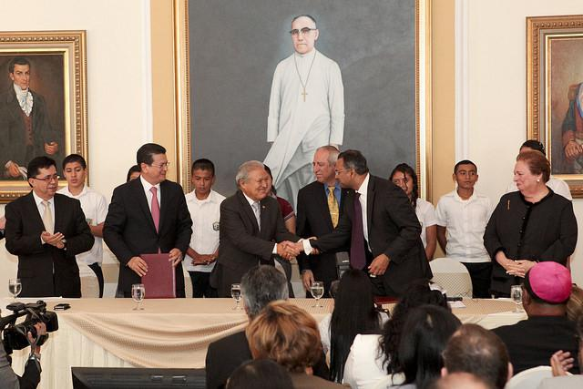 Beneath a painting of Archbishop Oscar Romero, Salvadoran President Sánchez Cerén shakes hands with a representative of the Millennium Challenge Corporation, while U.S. Ambassador Mari Carmen Aponte looks on. (Juan Quintero / U.S. Embassy)