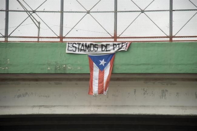 "A flag hangs from a highway overpass that reads ""Estamos de pie,"" in Caguas, Puerto Rico, Oct. 2, 2017. (U.S. Air Force photo by Airman 1st Class Caleb Nunez)"
