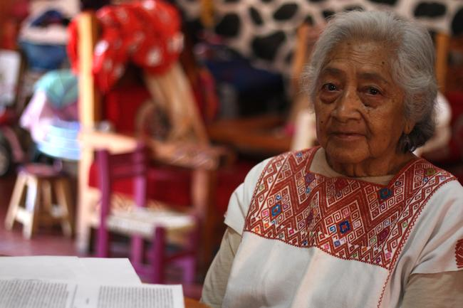 Osbelia Quiroz, one of the leaders of the resistance, sits at home beside legal documents in front of her. (Photo by Jose Olivares)