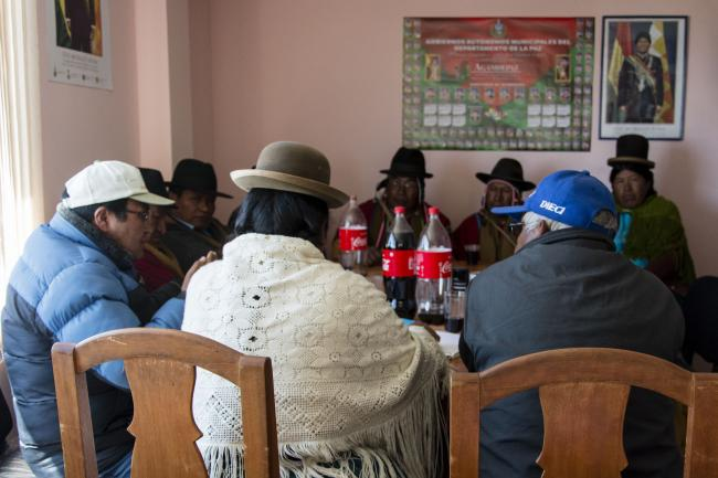 Bertha Quispe (center) meets local authorities in the town hall to discuss irrigation projects. They wear red ponchos, a sign of authority for the Aymara. (Photo by Irene Escudero)