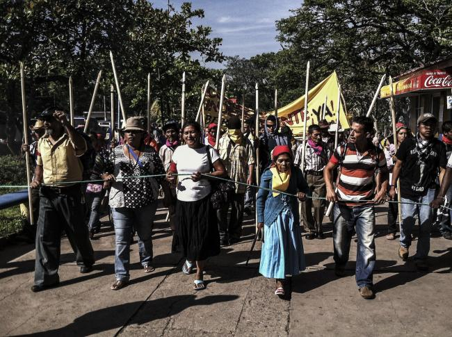 Vásquez, center, leads march to Presidential Palace to demand a just trial for Berta Cáceres' assassination, Tegucigalpa. The poles, representing authority, are used by Lenca elders. (Photo by Beverly Bell)