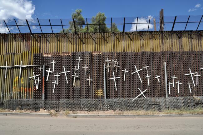 Crosses on the U.S.-Mexico border wall in Nogales, Sonora, commemorate migrants who have died while trying to cross into the United States (Jonathan McIntosh/Flickr)