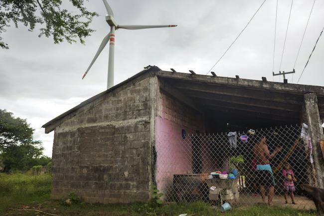 A wind turbine towers over a family's home in Union Hidalgo, Oaxaca. (Prometeo Lucero)