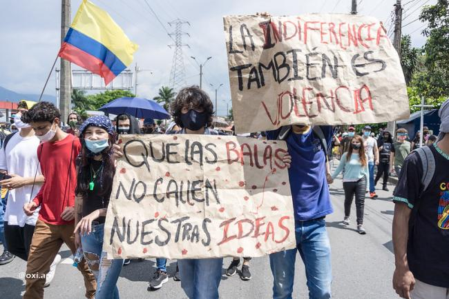 """Demonstrators in Colombia carry signs reading """"Indifference is also violence"""" and """"The bullets will not silence our ideas,"""" May 5, 2021. (Oxi.Ap / Flickr / CC BY 2.0)"""