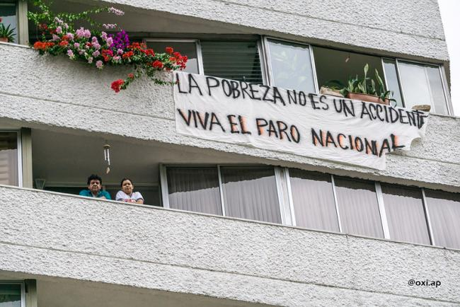 """A banner on the side of a residence reads """"Poverty is not an accident, viva the national strike,"""" May 5, 2021. (Oxi.Ap / Flickr / CC BY 2.0)"""