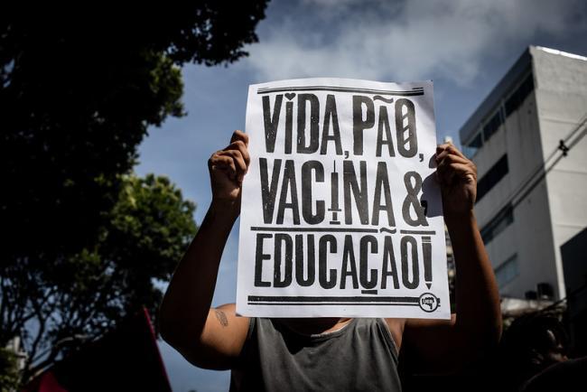 "During a demonstration in Salvador, Brazil, against Bolsonaro, May 29, 2021, a demonstrator holds a sign: ""Life, bread, vaccines, education!"" (Rafaela Araújo / Mídia NINJA / CC BY-NC 2.0)"