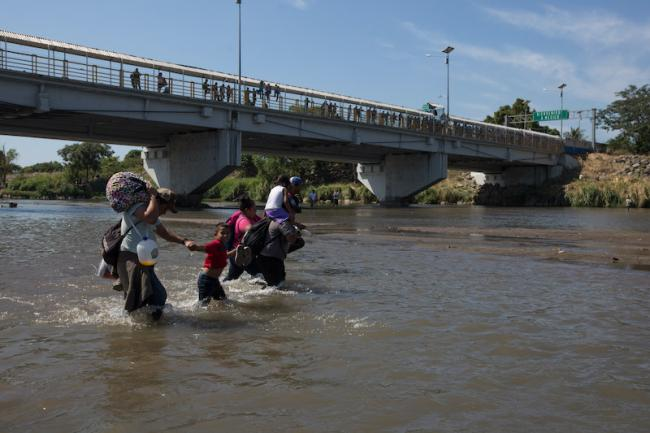 A family crosses the Suchiate River as part of the caravan of migrants on January 20 (Photo by Jeff Abbott)