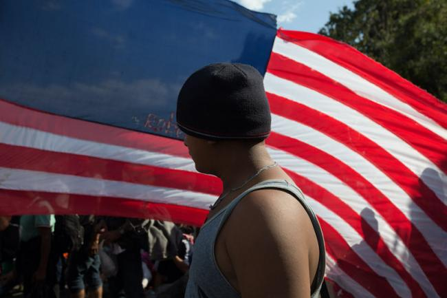 A Honduran migrant stands in front of a home made US flag on January 23 (Photo by Jeff Abbott)