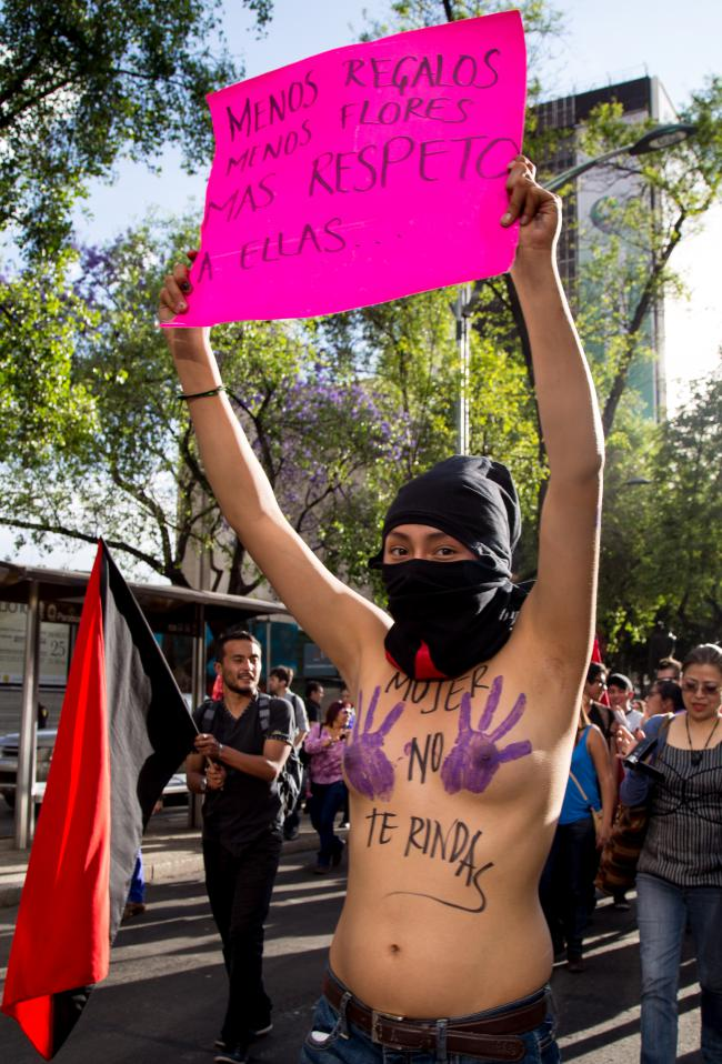 """International Women's Day 2014, Mexico City. Sign reads, """"Fewer gifts, fewer flowers, more respect [for women]."""" Body art reads, """"Woman, don't give up."""" (Rotmi Enciso / Producciones y Milagros Agrupación Feminista)."""
