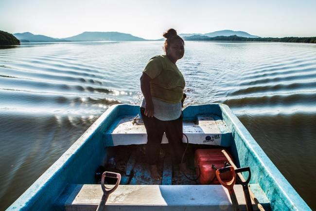 A member of the Mangrove Fisherwomen's Cooperative sets out in a small fishing boat, known as a lancha. (Antonio Cascio)