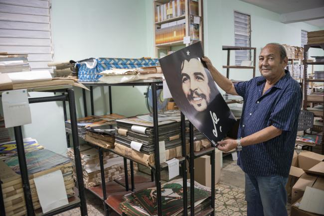 """Rafael Enríquez Vega, diseñador e ilustrador de la OSPAAAL en el almacén de la sede de la Revista Tricontinental mostrando su afiche del """"Ché sonriente"""" (junio de 2019). (Foto por Fernando Camacho Padilla)"""