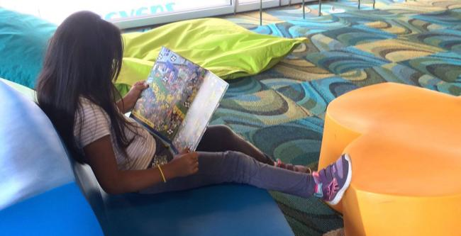 A child reads in a U.S. library as part of the REFORMA Children in Crisis Task Force, which provides bilingual books to refugees from Central America across the U.S. (REFORMA/Facebook)