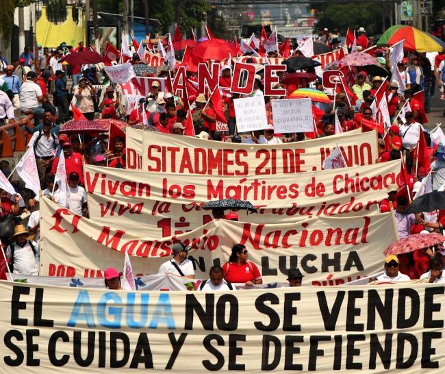 Demonstrators carry signs against water privatization at a May Day march in El Salvador. (Photo by CISPES)