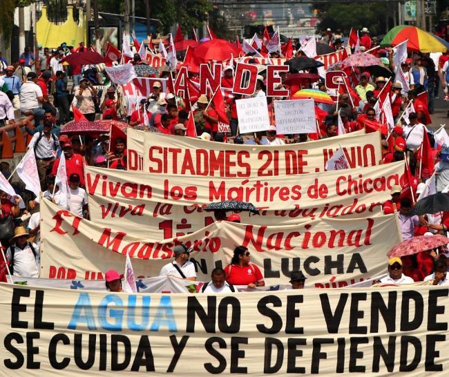 Manifestantes portan pancartas en contra de la privatización del agua, en la marcha del Día Internacional de los Trabajadores en El Salvador. (Foto por CISPES)