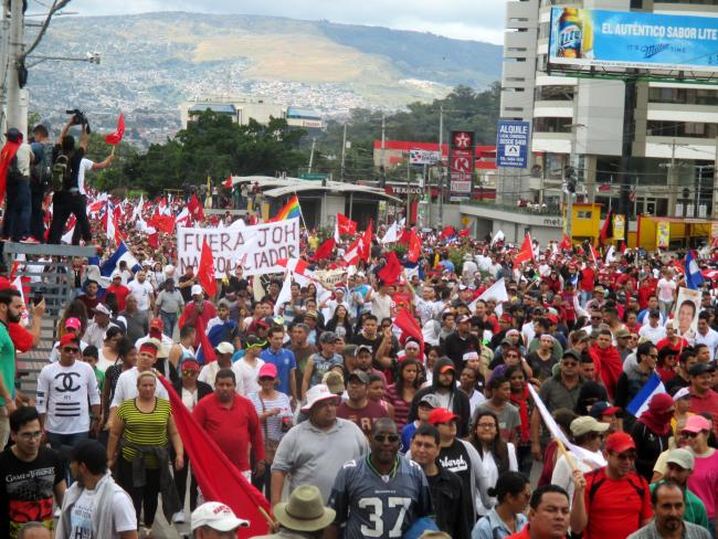 """Out with narco-dictator JOH"" reads a banner referring to president Juan Orlando Hernández (JOH) at a march in Tegucigalpa on December 3, when tens of thousands of Hondurans hit the streets around the country to protest electoral fraud. (Photo by Sandra Cuffe)."