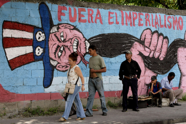 """People pass in front of a mural reading """"Down with imperialism"""" in Caracas, December 1, 2006. (Reuters / Rickey Rogers / Alamy Stock Photo)"""
