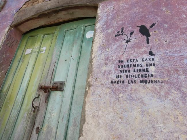"""A door in Suchitoto, El Salvador with a stencil reading """"In this house we want a life free a violence against women."""" (Miller Gruppe, Pixabay)"""