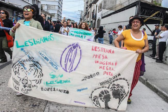 "Sign reclaiming marginal LGBT identities reads, ""Lesbian, imprisoned, indigenous, black, whore, dyke, carpet muncher, I'm lesbian because I feel like it, direct action, dignity, resistance."" (Producciones y Milagros Agrupación Feminista)"