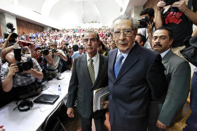 Enfrían Ríos Montt accompanied by his lawyers, leaving Guatemala City courtroom after being sentenced to 80 years in prison for genocide and crimes against humanity, May 10, 2013, Guatemala City. (Daniel Hernández-Salazar / Dictator in the Dock)