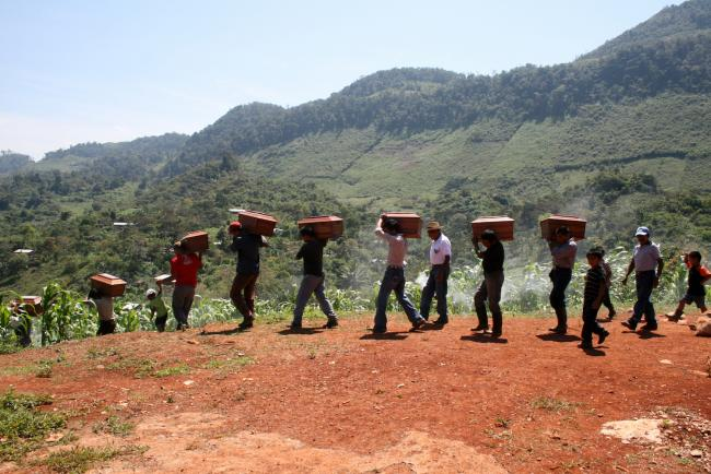 Queqchí people carrying their loved one's remains after an exhumation in the Ixil region of Guatemala, in 2012 (Cafca Archive/ Wikimedia Commons)