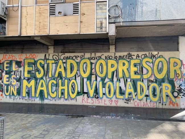 "A graffitti mural reading, ""THE OPPRESSIVE STATE IS A MACHO RAPIST,"" city center, Santiago. (Terri Gordon-Zolov)"