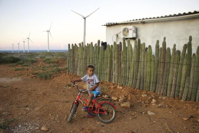 Nancy Gutierrez's son plays outside their home, located just 200 yards from the Jepírachi wind farm. (Photo by Christina Noriega)