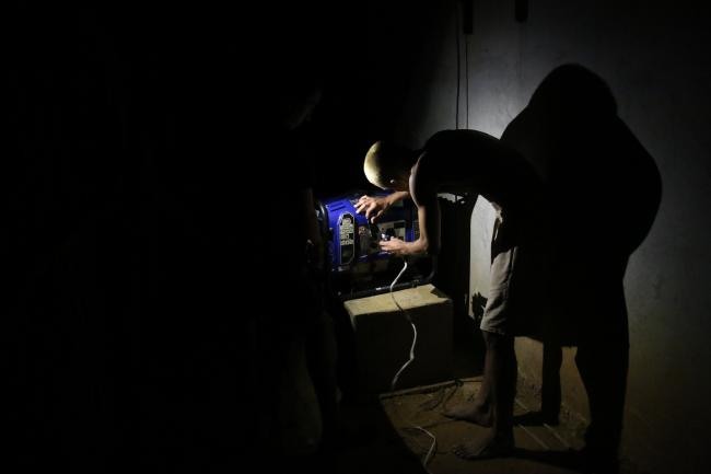 Nancy Gutierrez's home doesn't have electricity. Here, a guest at her house tries to fix the broken power generator at night. (Photo by Christina Noriega)