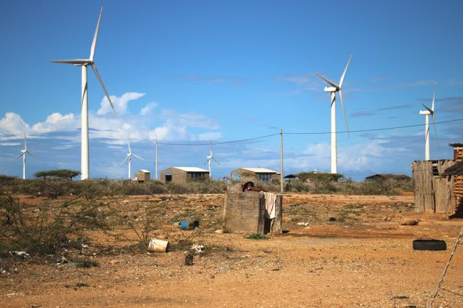 A girl from the Aerutkajui community brushes her teeth in a roofless bathroom, Jepírachi wind turbines appear in the background. Despite the wind farm benefits, some families don't have running water or adequate housing. (Photo by Christina Noriega)