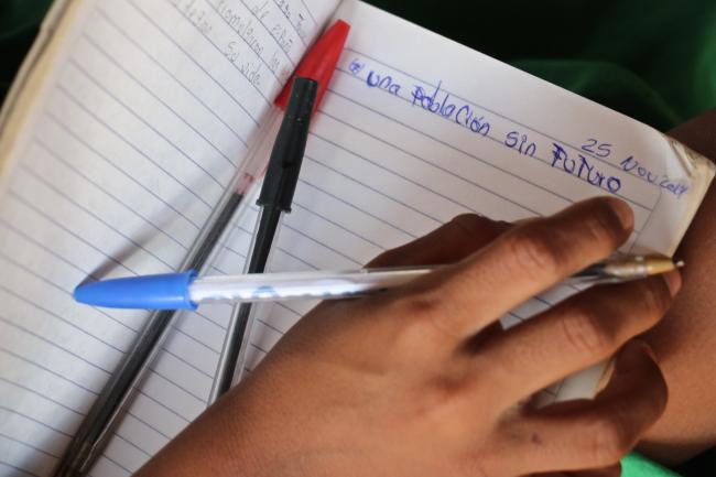 """A page from a student's notebook during a day of class in Jasaainmou. """"A population without future,"""" it reads. (Photo by Christina Noriega)"""