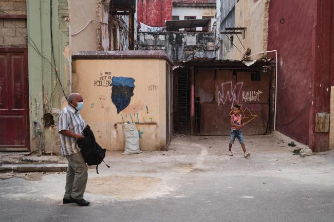 """An old man and a boy walk in front of a wall painting of a black man saying """"I am not a killer"""" in Central Havana. (Natalia Favre)"""