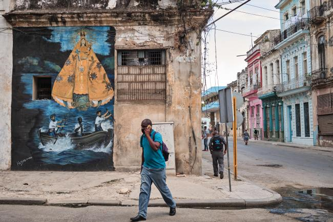 A man walks in front of a painting of the Charity Virgin of Copper, Cuba's patron saint, in Old Havana. (Natalia Favre)