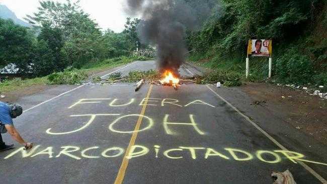 "A highway protest on December 1 against vote tampering in favor of President Juan Orlando Hernández, popularly known as JOH - ""Get Out JOH, narco-dictator!"" (Honduras Solidarity Network)"
