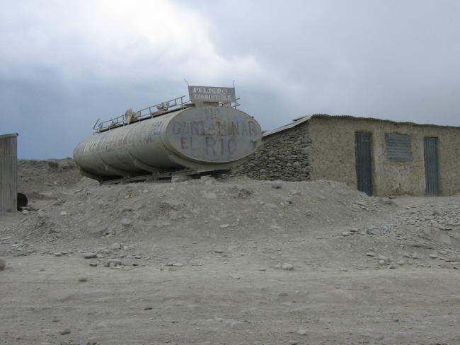 "Fading graffiti from a protest against off-thebooks gold mines on a fuel tank in Ananea, Peru, reads, ""Don't pollute the river."" Heavy equipment such as this fuel tank were financed by the regional Ministry of Energy and Mines. (Heather Williams)"