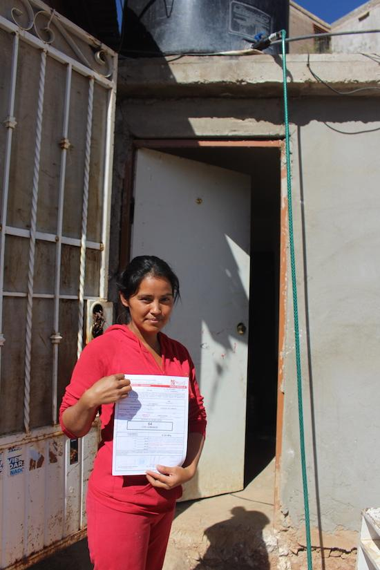 Cristina Navarro displays a certificate of occupancy for her home in Colosio, a step in the way to getting legal recognition. (Noah Silber Coats)