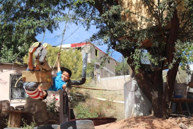 Kids play on a swing in the Colosio neighborhood. (Noah Silber Coats)