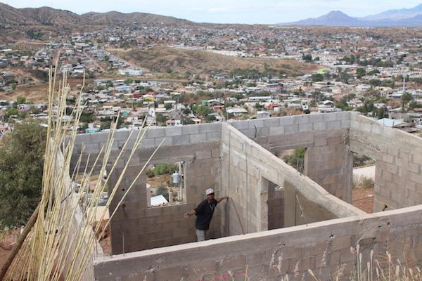 """A man works on a concrete-block home in Colosio. """"Take a photo to show that I'm out here working,\"""" he said. (Noah Silber Coats)"""