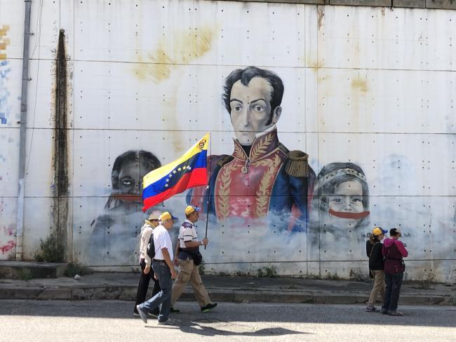 Partidarios de Juan Guaidó pasan por un mural de Simón Bolívar en su camino hacia una manifestación en enero de 2019 en Caracas (foto por Rebecca Hanson).