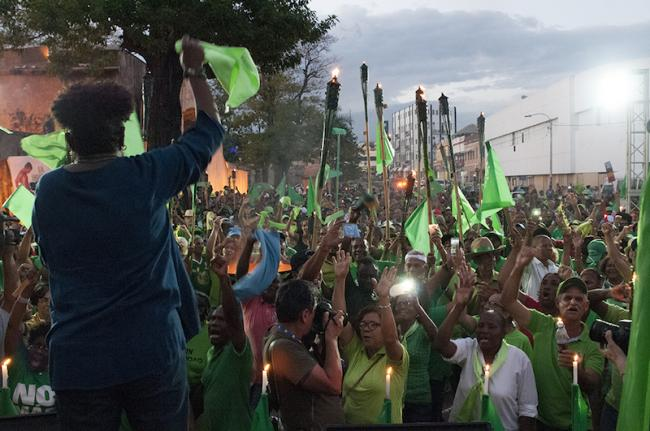 """Singer Xiomara Fortuna speaking to Green March supporters at Parque Independencia in Santo Domingo, capital of the Dominican Republic, holding the """"Green Torch"""" which toured the country in March to symbolize the fight against impunity and government corruption. (Lorena Espinoza Peña)"""